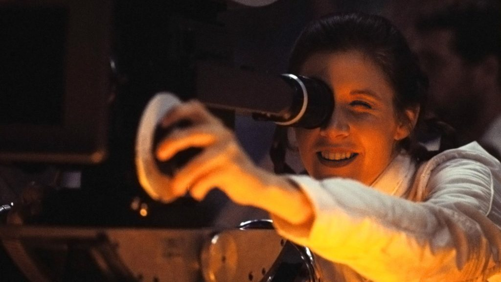 Carrie Fisher peers through a film camera in a behind the scenes photo from The Empire Strikes Back.