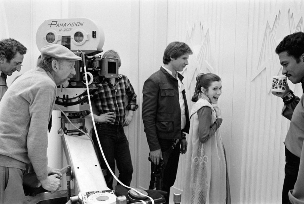 Carrie Fisher shares a laugh with Harrison Ford, Billy Dee Williams, and Irvin Kershner in a behind the scenes photo from The Empire Strikes Back.