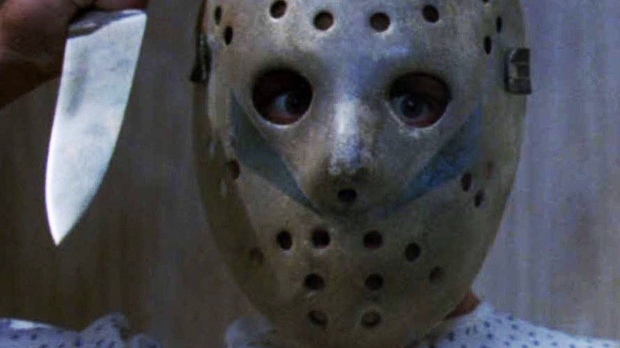 Close up of Jason Voorhees in his hockey mask a butcher knife raised and pointed toward the camera.