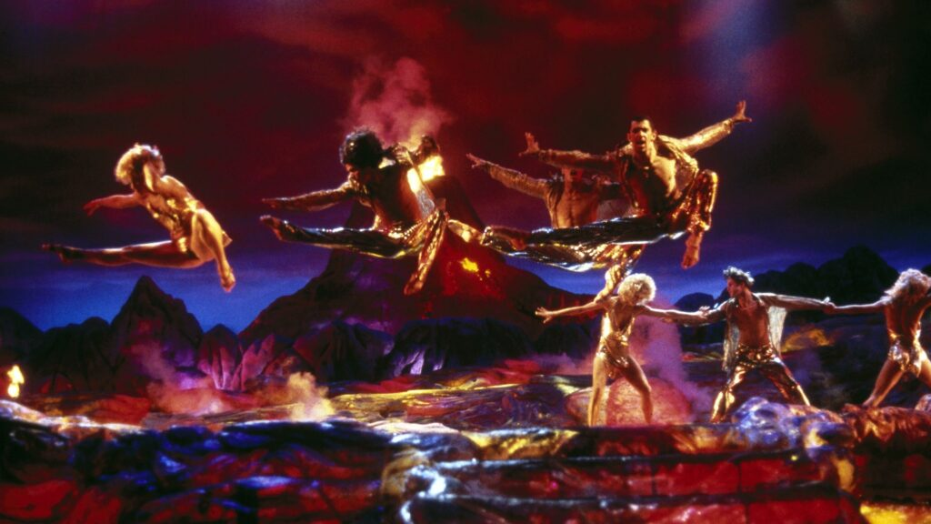 Male dancers in gold suits leap into the air on a rocky set complete with a volcano in this 90s Verhoeven film.
