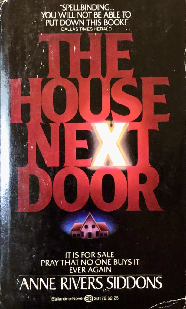 "Paperback horror novel cover featuring the title ""The House Next Door"" in deep red tones with a small illustration of a house below."